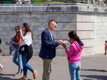 Man signs petition, Paris, France. PARIS, FRANCE - MAY 9, 2018: A man signs a petition held by a young woman in front of the Sacre Couer, Montmarte. Travel and stock photos