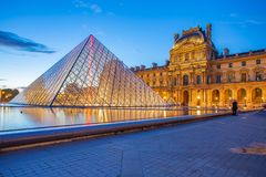 Pyramid Glass with view of Louvre Museum at night in Paris stock photos