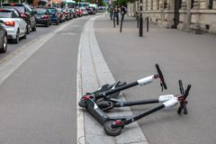 PARIS, FRANCE - MAY 25, 2019: Scooter kicksharing lying on the sidewalk. Scooter startups have flooded the city`s royalty free stock images