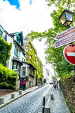 Paris, France - May 27, 2015: street in paris in the Montmartre area on a sunny day with green trees and a blue sky. The Montmartre - one of the most famous Royalty Free Stock Photography