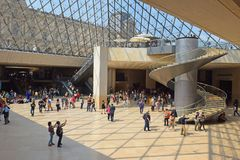 Tourists in the central hall under the Louvres pyramid in Paris. PARIS, FRANCE -23 may 2018 : tourists in the central hall, inside the Louvres pyramid before the Stock Photos