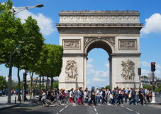 PARIS, FRANCE - MAY 24, 2015: Tourists walking on street in front of  Triumph Arc view on a sunny day. Triumph Arc view on a sunny day Paris Stock Photography