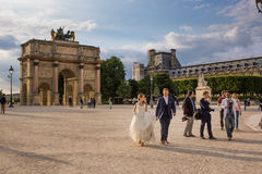 Paris, France May 26, 2015 Wedding party near the Louvre. A bride and groom posing for their wedding photos in the beautiful city of Paris Royalty Free Stock Images