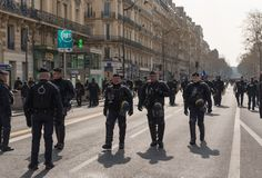 French riot police marching in the street during yellow vests Gilets jaunes protest in Paris. Paris, France - 22nd March, 2019: French policemen and armed forces royalty free stock images