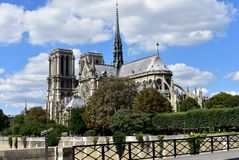 Paris, France. Notre Dame Cathedral from bridge over Seine river. Trees and river walk. Blue sky with clouds. royalty free stock image