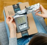 Woman unpacking unboxing Amazon Prime cardboard box HDD. PARIS, FRANCE - NOV 4, 2017: Curious woman unboxing on the living room armchair the Amazon Prime stock image