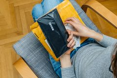 Woman unpacking unboxing Amazon Prime cardboard box. PARIS, FRANCE - NOV 4, 2017: Female photographer unboxing on the living room armchair the Amazon Prime stock images