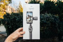 DJI Osmo Mobile 2 Smartphone Gimbal packaging. PARIS, FRANCE - NOV 22, 2018: Man hand holding in outdoor background new DJI Osmo Mobile 2 Smartphone Gimbal royalty free stock photos