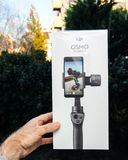 DJI Osmo Mobile 2 Smartphone Gimbal packaging. PARIS, FRANCE - NOV 22, 2018: Man hand holding in outdoor background new DJI Osmo Mobile 2 Smartphone Gimbal royalty free stock photo