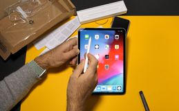 Man unboxing latest iPad Pro and Apple Pencil stock photo