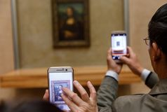 Leonardo Da Vinci`s Mona Lisa at the Louvre Museumn. PARIS, FRANCE - Nov 10, 2017: Visitors do selfie and take photo of Leonardo Da Vinci`s Mona Lisa at the stock images