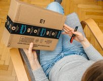 Woman unboxing unpacking amazon box. PARIS, FRANCE - NOV 4, 2017: Woman holding cutter preparing to unbox the Amazon Prime large cardboard box with Prime scotch stock photo