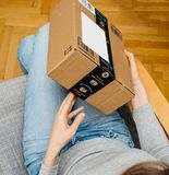 Woman unboxing unpacking amazon box. PARIS, FRANCE - NOV 4, 2017: Woman point of view holding new Amazon Prime large cardboard box with Prime scotch sealing tape stock photography