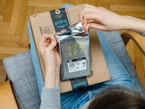 Woman unpacking unboxing Amazon Prime cardboard box HDD. PARIS, FRANCE - NOV 4, 2017: IT woman unboxing on the living room armchair the Amazon Prime cardboard stock photography