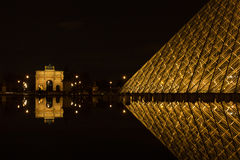PARIS,FRANCE - NOVEMBER 05: Entrance to Louvre Museum and Arc de. Triomphe du Carrousel on November 05, 2012 in Paris. The crystal pyramid was completed in 1989 Royalty Free Stock Photography