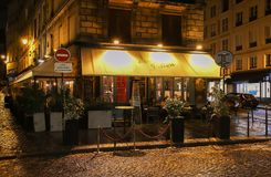 The traditional French cafe Chez Julien at rainy night , Paris, France. Paris, France-November 10 , 2018: The cafe Chez Julien situated in a busy corner of the stock photos