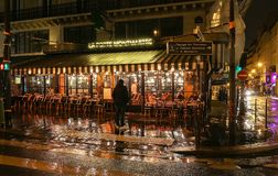 The famous cafe La porte Montmartre on Grands boulevards at rainy night , Paris, France. Royalty Free Stock Image