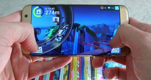 Man Playing A Racing Game On His Smartphone. Paris, France - November 17, 2018: Man Playing MMX Hill Dash 2 Video Game On His Modern Smartphone Samsung Galaxy S7 stock video footage