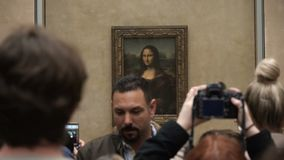 Visitors take photos of Leonardo DaVinci`s `Mona Lisa` at the Louvre Museum stock footage