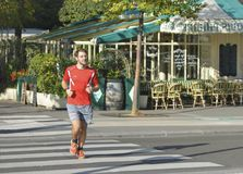 PARIS, FRANCE - OCTOBER 16, 2016: Amateur runner runs near a cafe on the street of Paris. France royalty free stock images