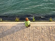 Girl sitting on the banks of the Seine in Paris royalty free stock photo