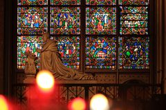 Paris, France - October 28, 2018: Interior of Notre Dame de Paris cathedral. Small altar with ancient statue and stained glass. Window and blurred offering royalty free stock photos