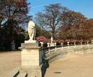 Luxembourg garden in the fall, Paris. Paris, France - October 17, 2005:The Luxembourg Garden in the Fall. In the foreground is a sculpture of a lion stock image