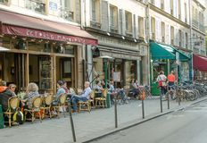 Many Parisians and tourists prefer the sidewalk tables at bistros and cafes royalty free stock photo