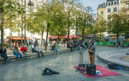 A musicians entertains young people sitting around a fountain Paris, France royalty free stock photo