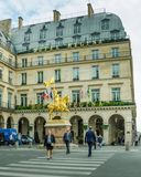 Parisians walk along Rue de Rivoli in front of Hotel Regina royalty free stock image