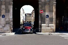 Paris, France. A very old Citroen 2CV car runs in the oldest square of the city, Place des Vosges. royalty free stock photo