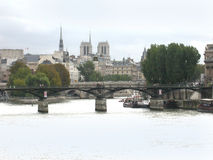 Paris France River Seine. A view showing a section of the River Seine in Paris France with Notre Dame's two towers in the backgound and a bridge in the Royalty Free Stock Photography