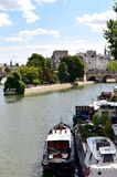 Paris, France. Seine River with boats and Ile de la Cite from Pont des Arts. View of Vert Galant Square with park. 17 Aug 2018. Ile de la cite and Square Vert stock photo