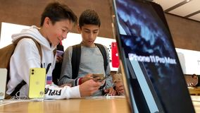 Apple Computers iPhone 11 Pro and Pro Max goes on sale. Paris, France - Sep 20, 2019: Young multi-ethnic group of boys looking at the new iPhone 11 Pro Max are stock footage