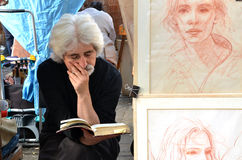 PARIS / FRANCE - September 24, 2011: Artist read a book in Montmartre, the legendary bohemian artist district of Paris. Next to th. E painter stands his work Stock Image