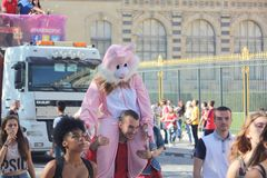 Paris France 24 september 2016 a boy who carries somebody with a costume of pink rabbit. Cheerful crowd in front of the museum of louvre at the techno parade royalty free stock photo