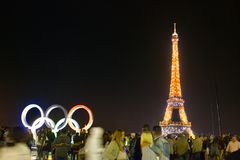 Eiffel tower, tourists in night hours and Olympic symbols. Paris, France - September 24, 2017: Eiffel tower in lights illumination and tourists swirl in night Royalty Free Stock Photo