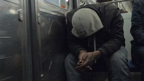 Homeless man in subway train hiding face under the hood. PARIS, FRANCE - SEPTEMBER 29, 2017: Homeless man in shabby clothes traveling by metro. He sitting in stock video