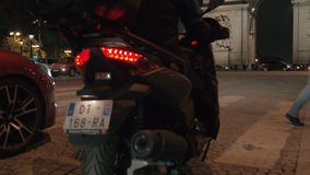 People and transport traffic in night Paris, view with Arc de Triomphe. PARIS, FRANCE - SEPTEMBER 29, 2017: Motorbike and cars waiting for the people to cross stock video footage