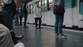 Subway train arriving to the station. Paris, France. Paris, France - September 29, 2017: People waiting at the platform and metro train arriving to the station stock footage