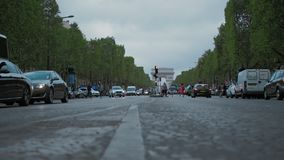 Paris France, Slow motion, Champs Elysees, the city's daytime traffic. Against the arch of triumph. Low angle view stock video