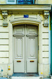 Paris, France - typical old apartment building. Wooden door. Beautiful flowers flowers at a parisian garden during summer time in a flowers store in Paris Royalty Free Stock Photo