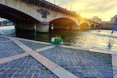 PARIS, FRANCE - VERS EN JUIN 2014 : Le jeune couple se repose sur la banque de la vue de dos de Siene Image stock