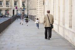 Paris, Frankreich - 12. April 2011: Junge Frau, die mit Kindern auf der Straße läuft lizenzfreies stockfoto