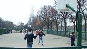 PARIS, FRANKREICH - DEZEMBER, 31, 2016 Jugendliche, die Straßenbasketball gegen Eiffelturm an einem nebeligen Tag spielen lizenzfreie stockfotos