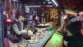 PARIS, FRANKREICH - DEZEMBER, 31 Weihnachts- und des neuen Jahresmarktfastfood klemmen Verkäufer fest Traditionelle Käsesandwiche stock video