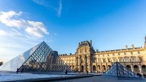 Paris, Frankreich Februar 2018: Louvre-Museumsansicht bei Sonnenuntergang, mit dem Glas der reflektierenden Wolken der Pyramide Lizenzfreie Stockbilder