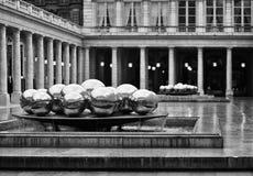 PARIS, FRANKREICH - 27. März 2011: Silberne Bälle im Brunnen reflektieren den Royal Palace-Hof Lizenzfreie Stockfotos
