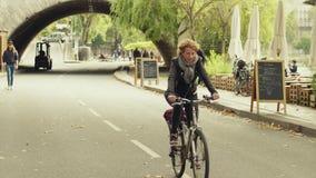 PARIS, FRANKREICH - 8. OKTOBER 2017 Frau, die durch Straßencafé entlang dem die Seine-Damm radfährt Lizenzfreies Stockfoto