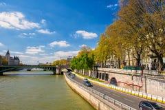 Paris Frankrike - 19 April, 2016: Bilar flyttar sig i gatan mellan Seine River, och guling lämnar träd Royaltyfria Bilder